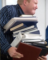 man with too much paperwork